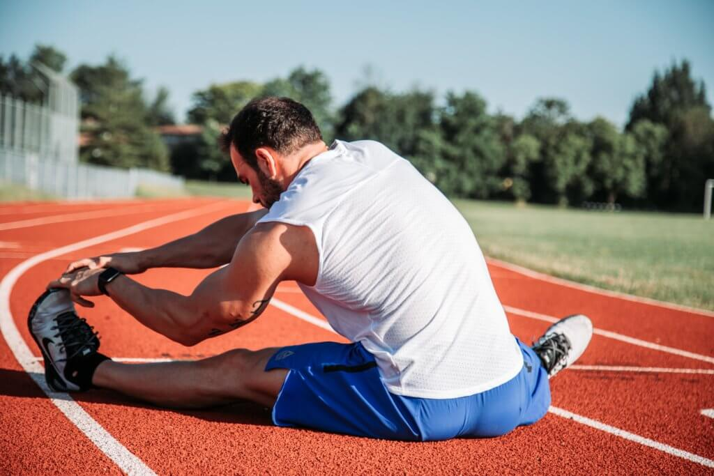 Man stretching his hamstring muscles to prevent injury- may not be the best option.